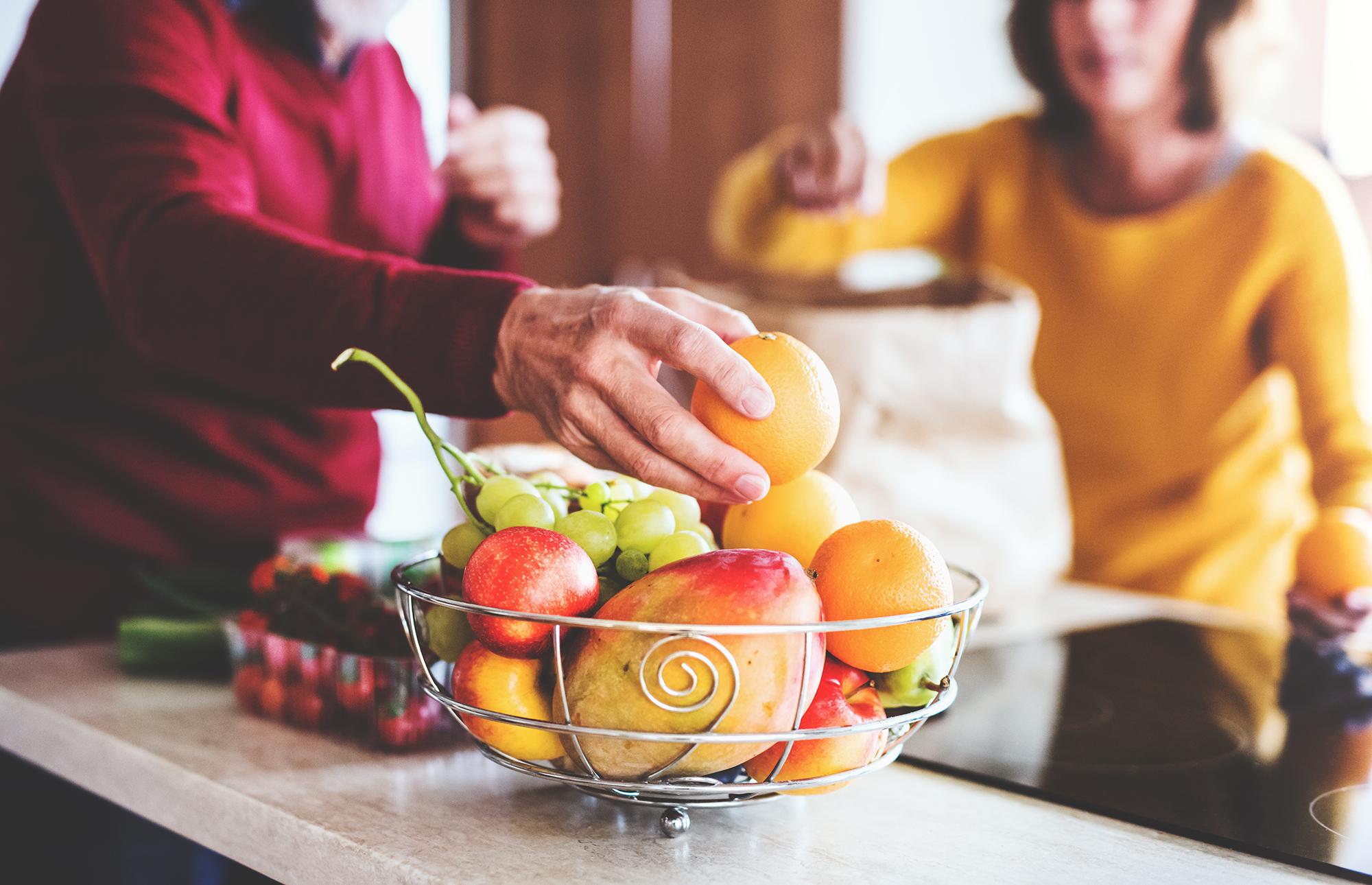 Seniors unpacking fruit in a bowl for healthy senior diet